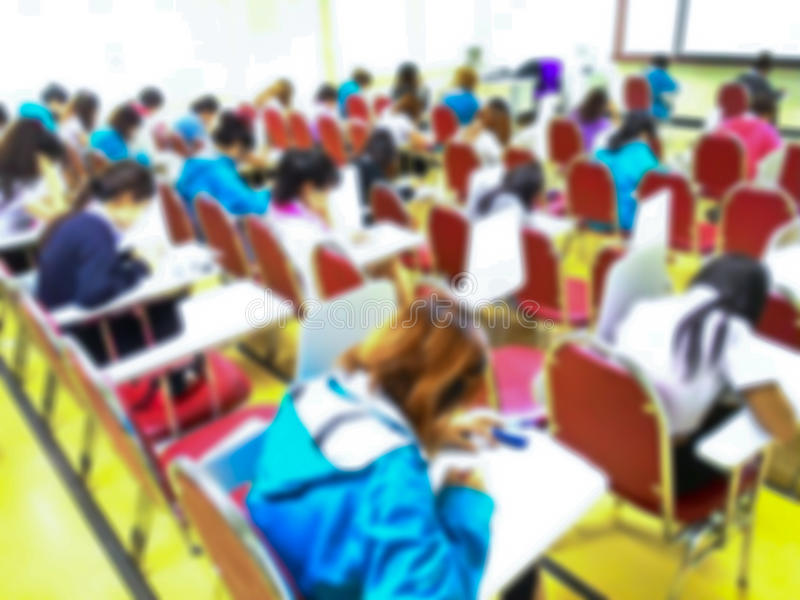 Soustrayez les étudiants brouillés faisant l'examen dans la chambre d'étude photographie stock libre de droits