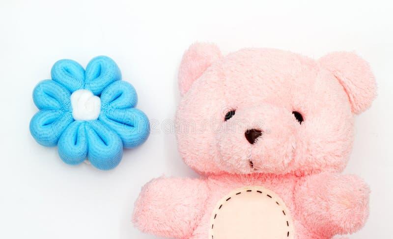 Soutenez l'ours rose mignon avec de belles fleurs bleues d'isolement dans le fond blanc images libres de droits