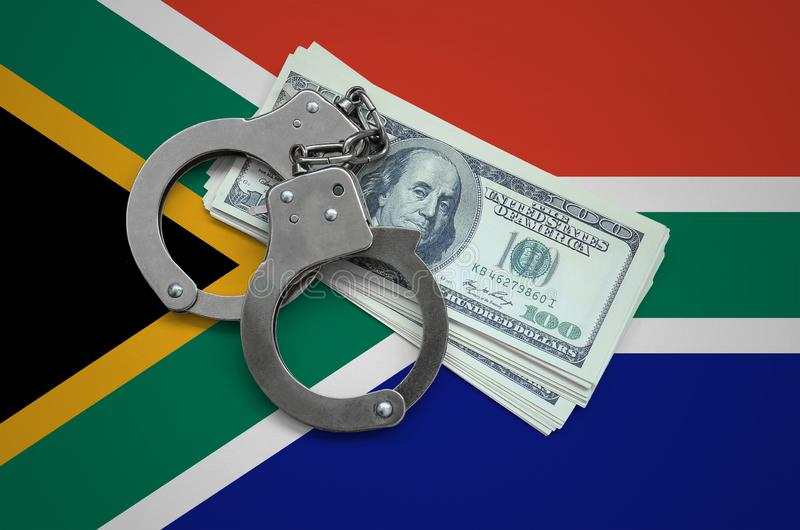 South Africa flag with handcuffs and a bundle of dollars. Currency corruption in the country. Financial crimes stock photography