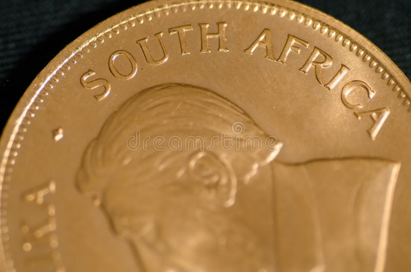 South Africa (word) on Gold Krugrand Coin. On black background royalty free stock photo