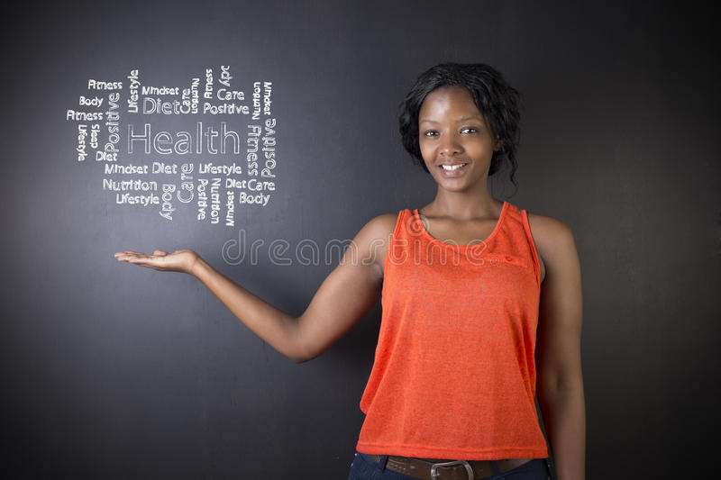 South African or African American woman teacher or student against blackboard background health diagram. South African or African American woman teacher or stock images