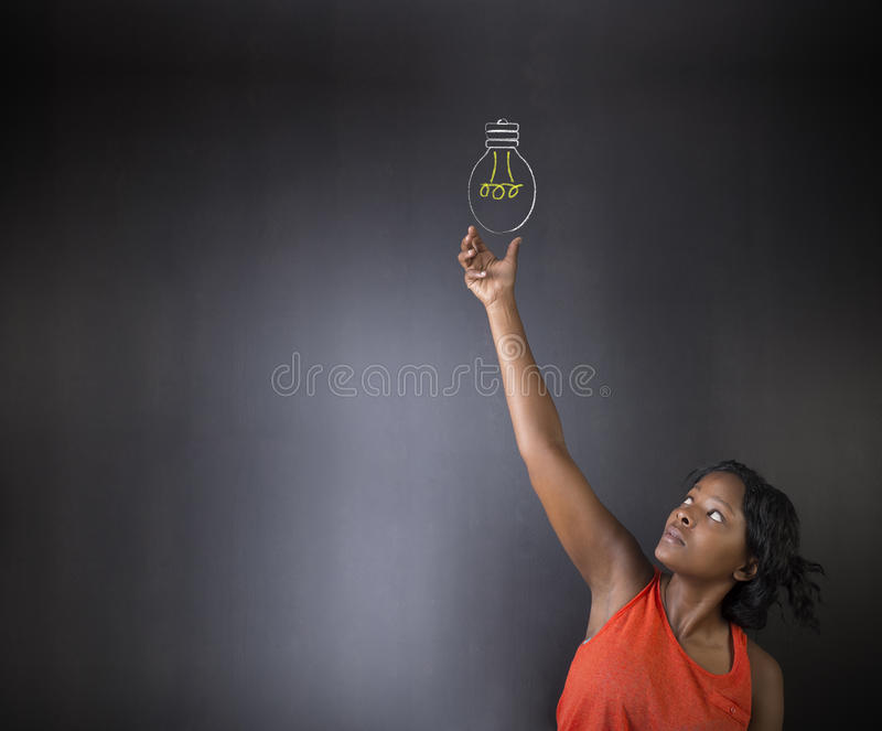 South African or African American woman teacher or student bright idea chalk lightbulb thinking blackboard background stock photography