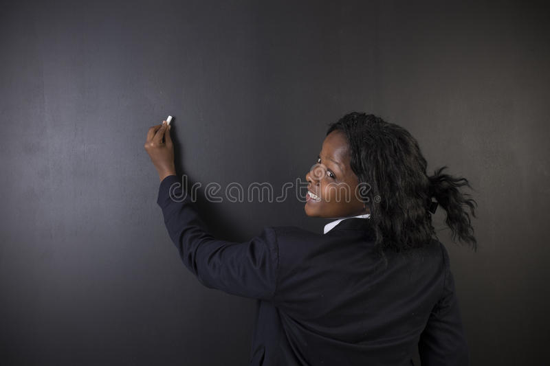 South African or African American woman teacher writing on chalk board stock photo