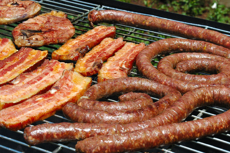 South African Braai. Grilled pork meat, lamb chops and sausages on a grill for a barbecue (South African Braai) outdoors in South Africa royalty free stock photo