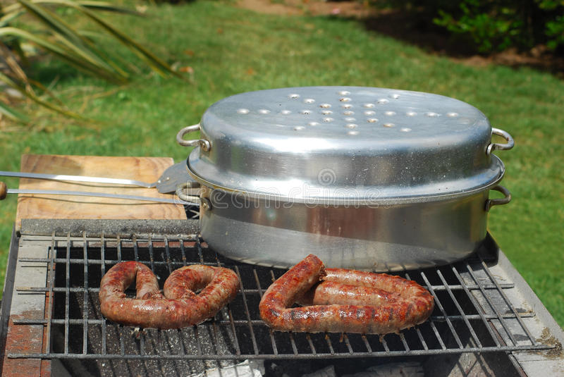 South African Braai scene. A typical and traditional South African barbecue with wurst and Braai pot in the garden outdoors royalty free stock photography