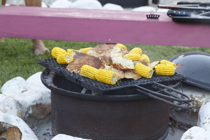 South African Charcoal Braai. Typical traditional South African braai, also known as a barbecue, cooked on hot coals over an open fire. With mielies corn and stock image