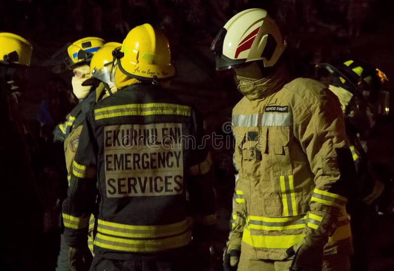 South African Firefighter in bunker gear - half length. South African Firefighters in full bunker gear at night preparing for teamwork stock photos