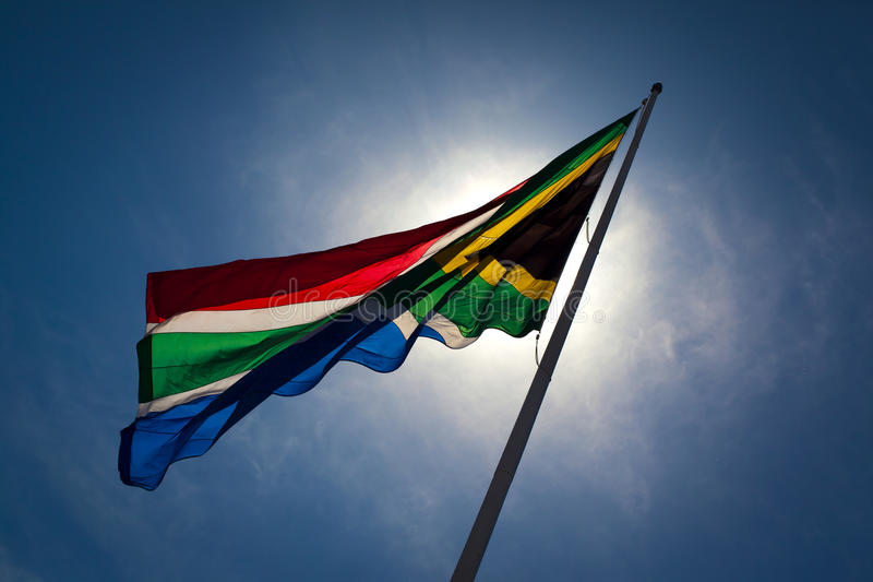 South-African flag. The South-African flag wavering in the wind against a blue sky with the sun shining from the back as a back light royalty free stock photo