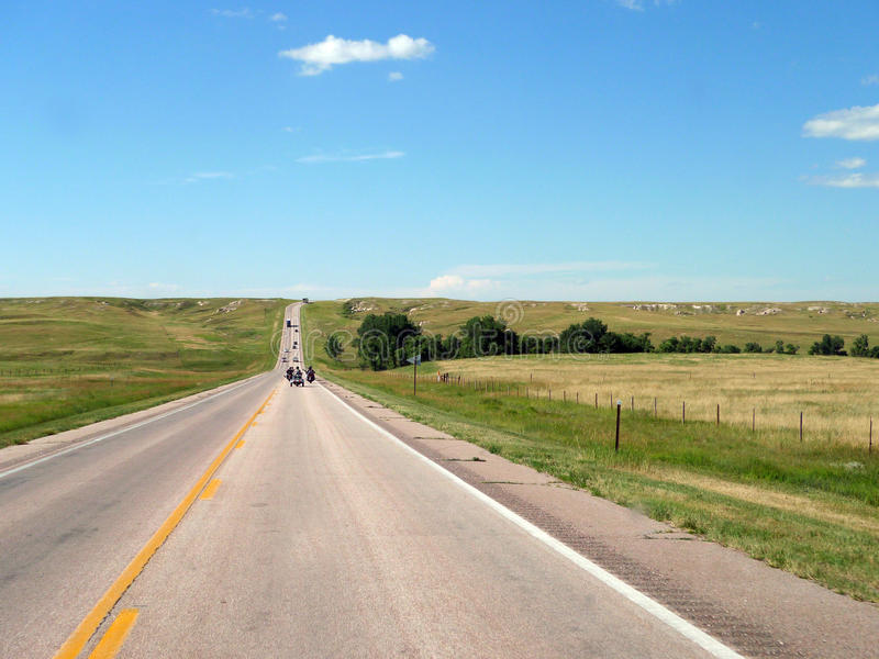 South Dakota open roads with rugged terrain, vehicles on roadway royalty free stock photo