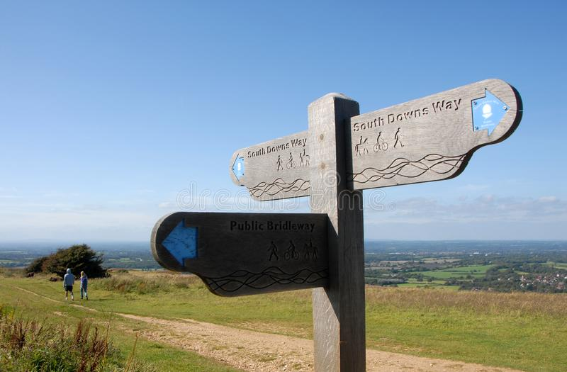 A signpost and a couple walking on the South Downs Way near Brighton in Sussex, England, UK. South Downs National Park, Sussex, England, UK. A man and a woman stock photos