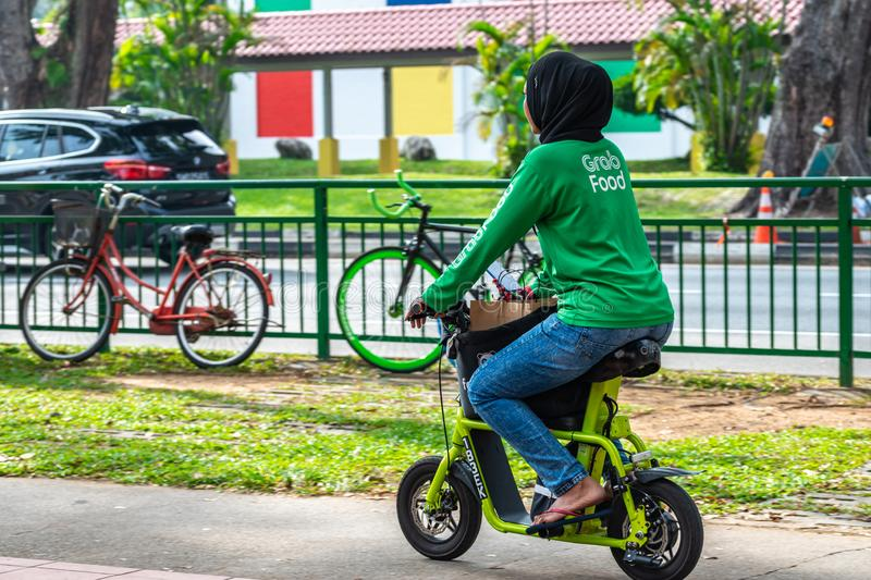 Asian Muslim Malay female with hijab food delivery rider on e-bike scooter. South East Asia / Singapore - Nov 9, 2019 : Asian Muslim Malay female with hijab head royalty free stock image