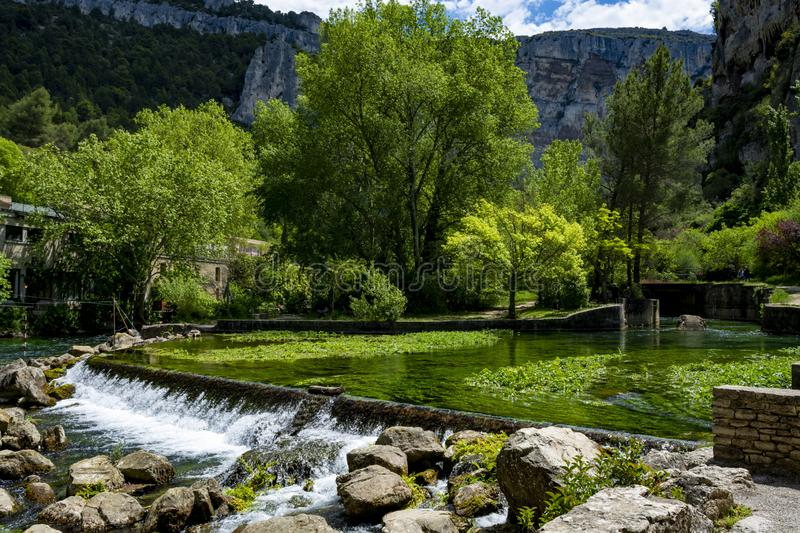 South of France, view on small Provencal town of poet Petrarch Fontaine-de-vaucluse with emerald green waters of Sorgue river. South of France, view on small royalty free stock image