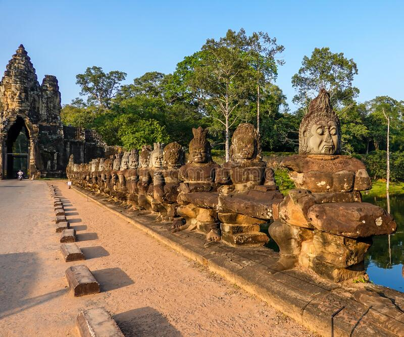 South gate bridge of Angkor Thom with statues of gods and demons royalty free stock image