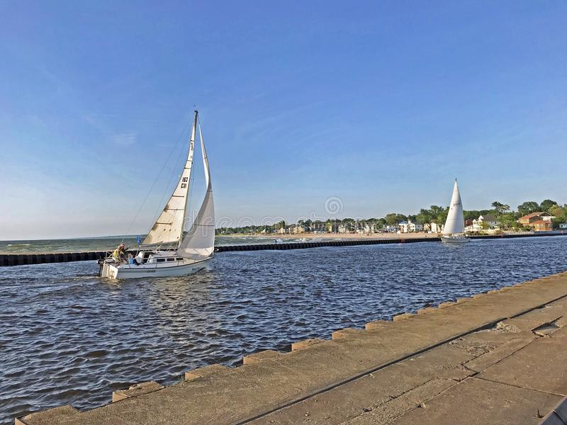 Two Sailboats Heading into South Haven Harbor stock photography