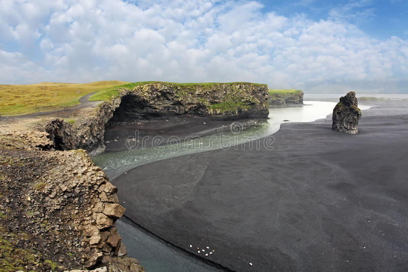 South Iceland - Dyrholaey coast. The black sand beach of Reynisfjara and the mount Reynisfjall from the Dyrholaey promontory in the southern coast of Iceland royalty free stock photography