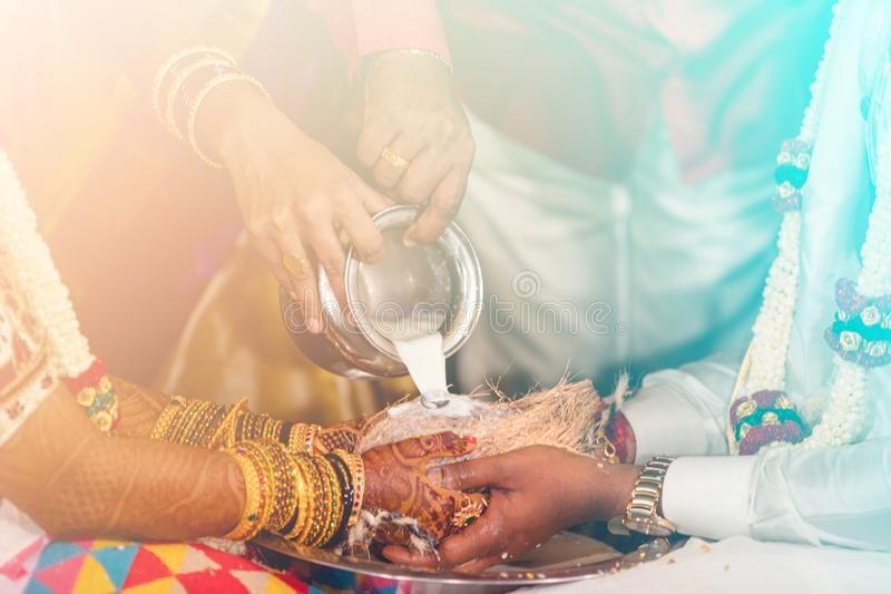 South indian bride and groom holding coconut. milk pouring ritual stock photography
