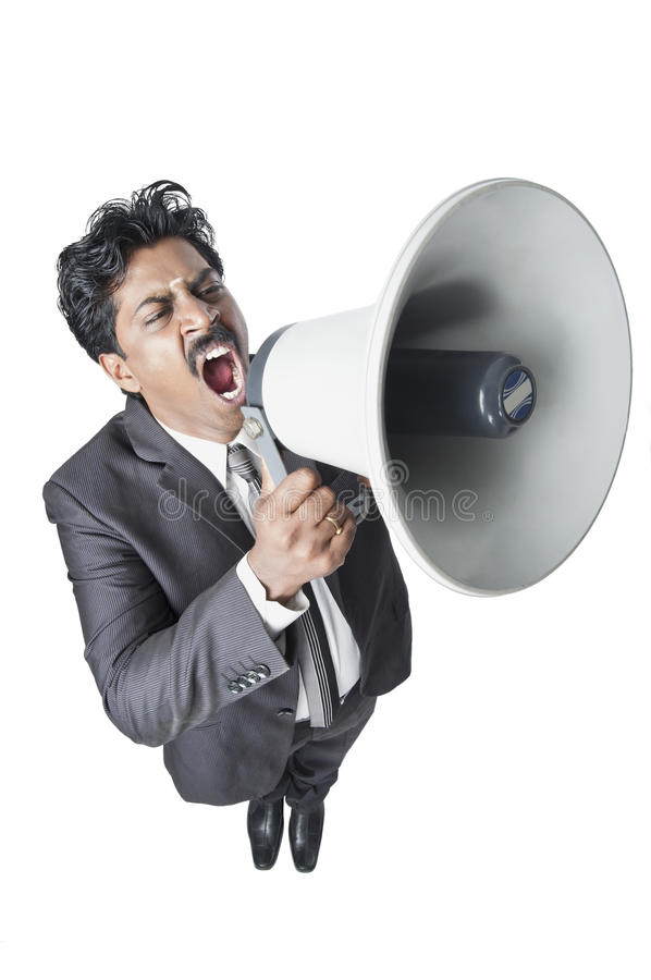 South Indian businessman shouting in a megaphone. High angle view of a South Indian businessman shouting in a megaphone stock images