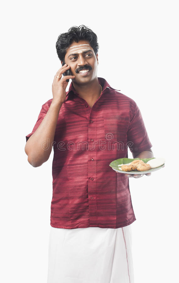 South Indian man holding a plate of food and talking on a mobile royalty free stock images