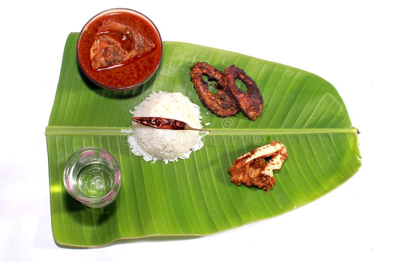 South indian meal rice with fish kulambu and crab. South indian meal rice with fish kulambu and crab, fish fry on a banana leaf stock photography