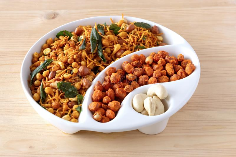 South indian spicy crunchy mix Nimco or Namkeen and spicy coated peanut white bowl wooden background stock images