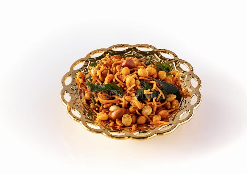 South indian spicy crunchy mix Nimco or Namkeen with peanut, rice, curry leaves and spice golden bowl background isolated royalty free stock photos