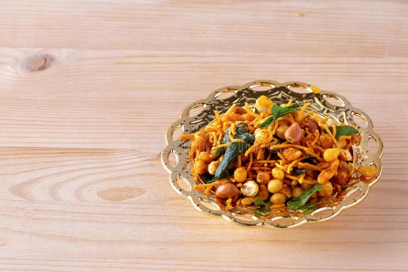 South indian spicy crunchy mix Nimco or Namkeen with peanut, rice, curry leaves and spice golden bowl background isolated.  royalty free stock photos