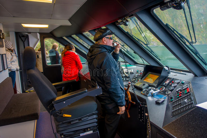 SOUTH ISLAND, NEW ZEALAND- MAY 25, 2017: Close up of a ferry boat pilot command cabin with a smiling captain holding a stock photo