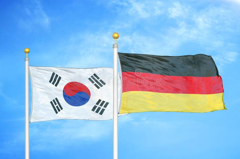South Korea and Germany two flags on flagpoles and blue cloudy sky. Background stock images