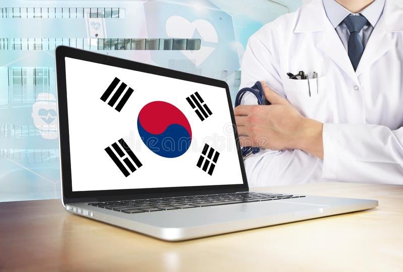 South Korea healthcare system in tech theme. Korean flag on computer screen. Doctor standing with stethoscope in hospital. Cryptocurrency and Blockchain stock photography