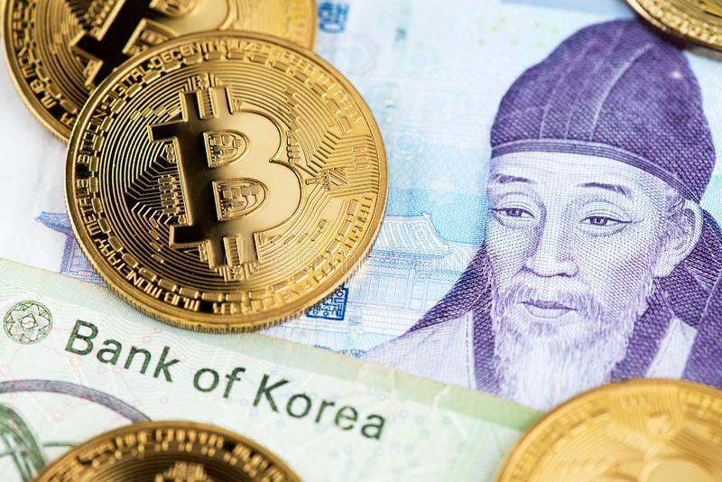 South Korea Won currency banknotes and Bitcoin cryptocurrency coins. South Korea Won currency banknotes and BTC Bitcoin cryptocurrency coins close up image royalty free stock image