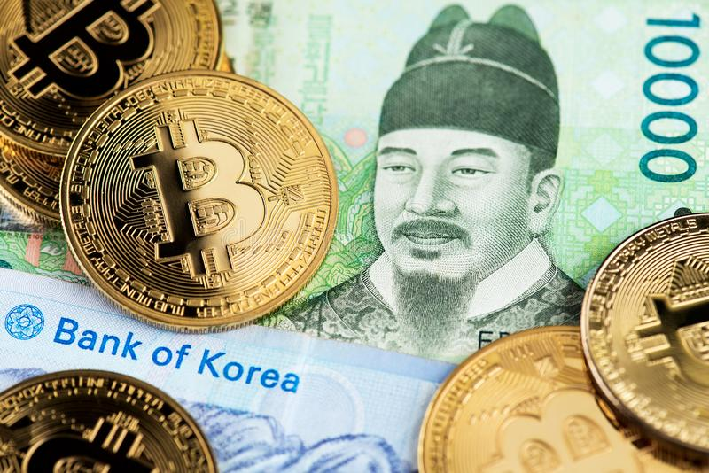 South Korea Won currency banknotes and Bitcoin cryptocurrency coins. South Korea Won currency banknotes and BTC Bitcoin cryptocurrency coins close up image stock image