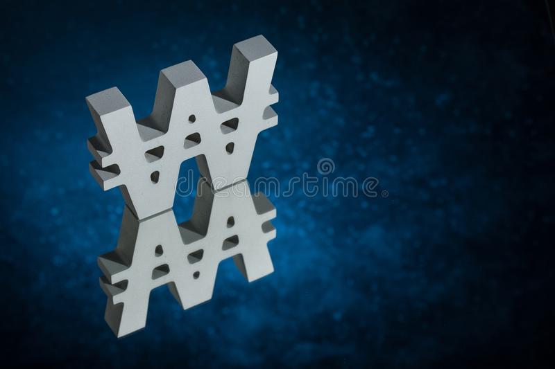 Won Symbol or Sign With Mirror Reflection on Blue Dusty Background. South Korean Currency Symbol or Sign Won With Mirror Reflection on Blue Dusty Background stock images