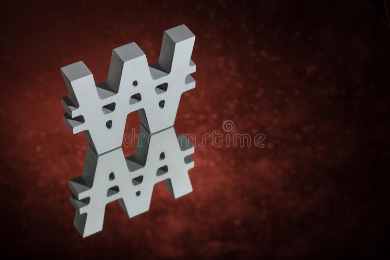 Won Symbol or Sign With Mirror Reflection on Red Dusty Background. South Korean Currency Symbol or Sign Won With Mirror Reflection on Red Dusty Background stock photos