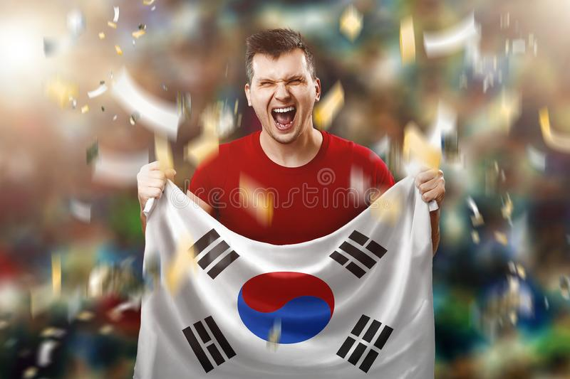 South Korean fan, a fan of a man holding the national flag of South Korea in his hands. Soccer fan in the stadium. Mixed media stock photos