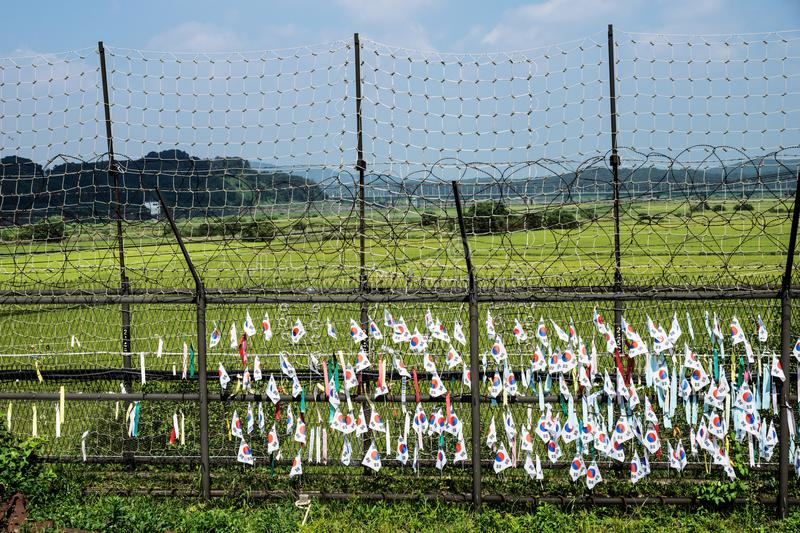 South korean flags at a fence at the demilitarised zone DMZ at the freedom bridge, South Korea, Asia. South korean flags and ribbons at a fence at the green stock image