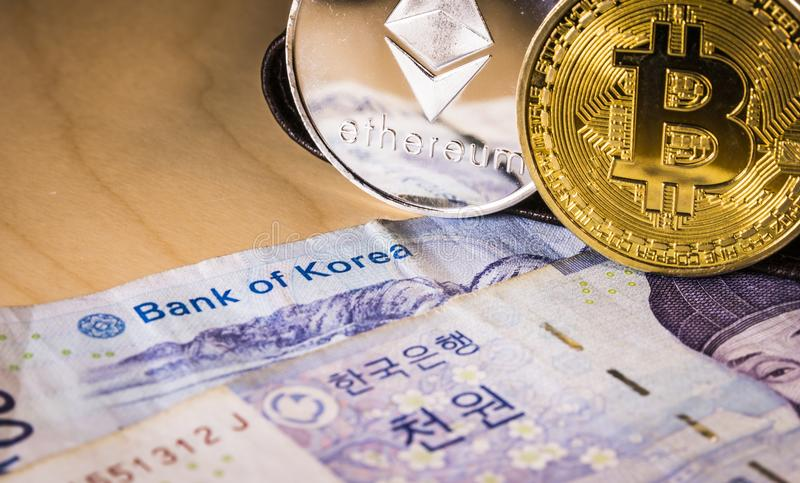South Korean won currency, bitcoin and ethereum. Business concept. South Korean won currency with the words bank of korea focused and physical bitcoin and stock photo