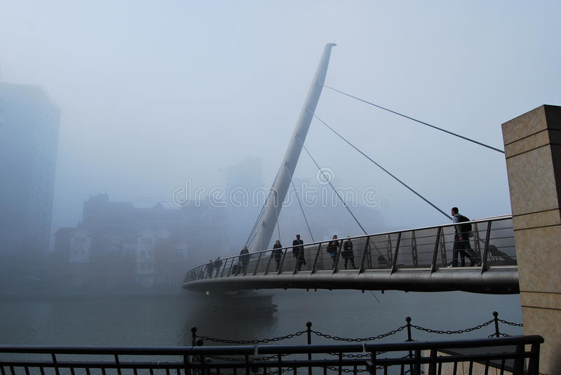 South Quay Footbridge in the Fog. South Quay Footbridge, West India Dock, London Docklands, in the early morning London fog. It looks dark, cold, damp and dismal royalty free stock images