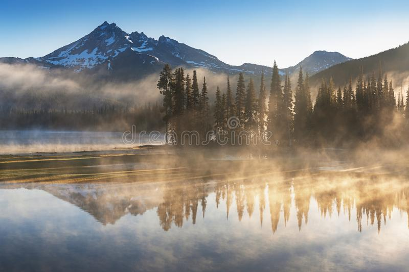 South Sister and Broken Top reflect over the calm waters of Sparks Lake at sunrise in the Cascades Range in Central Oregon, USA in. An early morning light royalty free stock image