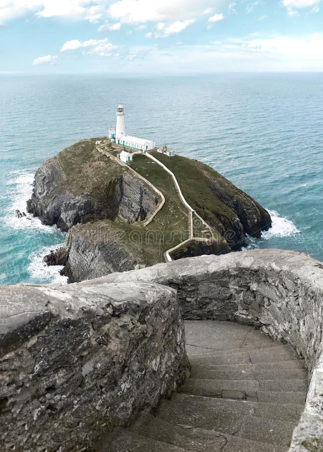 South Stack Lighthouse in North Wales. UK. In between blue Atlantic Ocean, crashing waves, cliffs and walkway stock photography