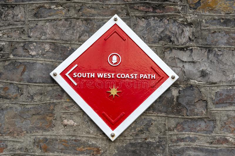 South West Coast path sign. On a wall in Plymouth UK. Plymouth, England, UK. August 2019. A red and white South West Coast Path sign mounted on a wall on the royalty free stock images