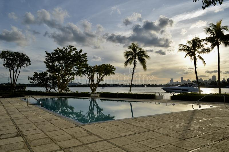 Southbeach Condo Pool at Sunset. A outhbeach condo pool at sunset with a motor yacht at anchor on the intra-coastal waterway and miami tall building skyline in royalty free stock image