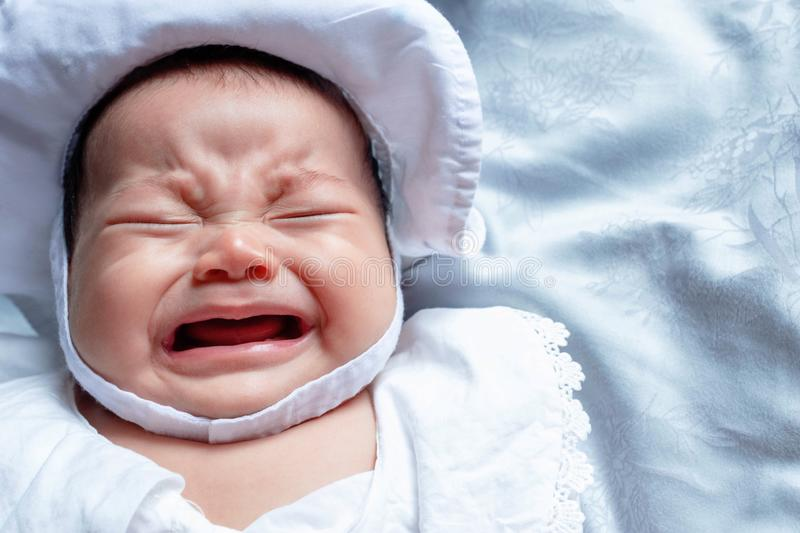 Southeast Asian baby colic is wearing white hat and shirt. South East Asian newborn is crying. Newborn is unhealthy. Infant is unhappy. Kid is on the white bed stock photos