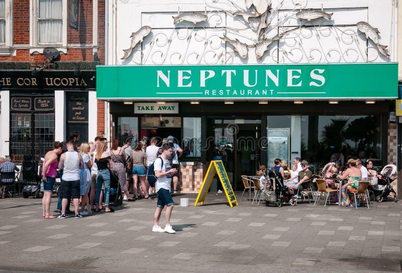 Southend, Reino Unido - 21 de abril de 2018: os Dia-excursionistas enfileiram-se para microplaquetas no restaurante de Neptunes n fotografia de stock royalty free