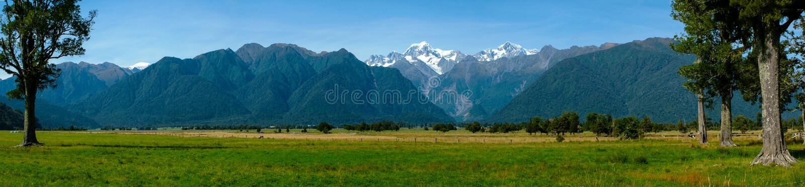 Southern Alps from Lake Matheson. Panoramic view of the Southern Alps, Mount Cook (Arakoa) and Mount Tasman from Lake Matheson stock photo