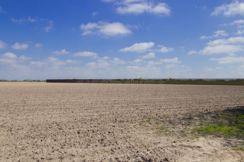 Southern border wall in Brownsville, Texas. Brownsville, TX - February 18, 2017: Border fence stretches on privately owned land, separating U.S. from Mexico. The stock photo