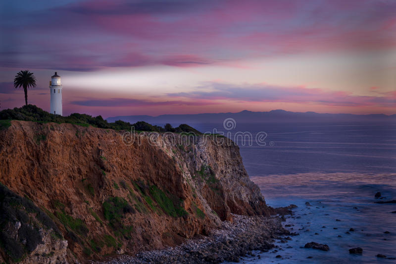 Southern California Lighthouse at sunset. A Southern California lighthouse shines at sunset with Catalina Island in the background stock photography