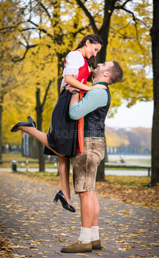Bavarian couple in Tracht in loving embrace with uplift. Southern German couple in Tracht in loving embrace, he is lifting her up stock photo