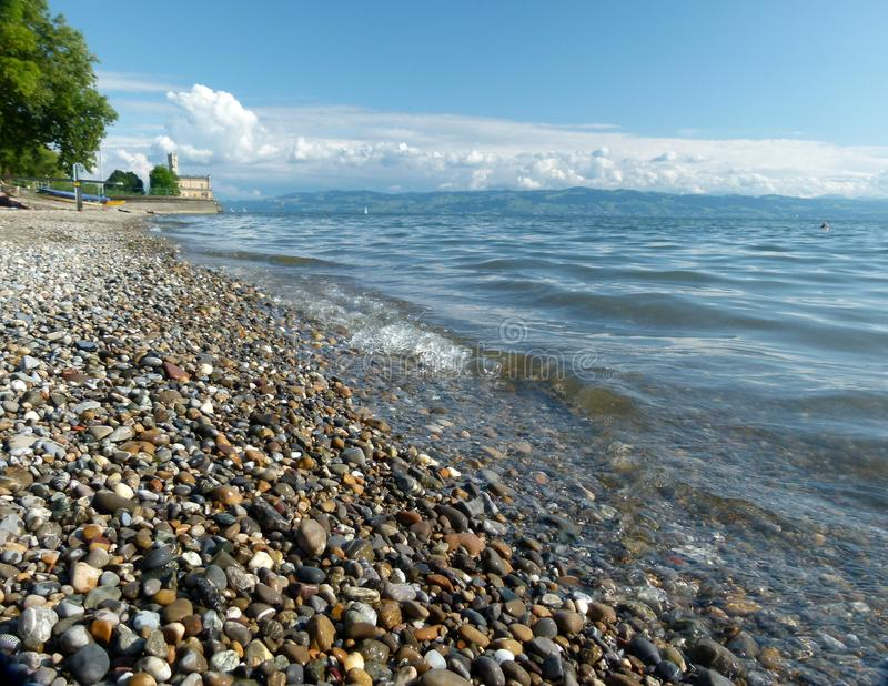 Lake with gravel beach and a water castle and great clouds in the background royalty free stock photography
