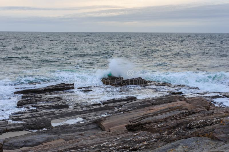 Southern Maine Rocky Atlantic Coastline. Rocky coast of Southern Maine with rolling surf and crashing waves, visitors have sweeping views of Casco Bay and the royalty free stock photo