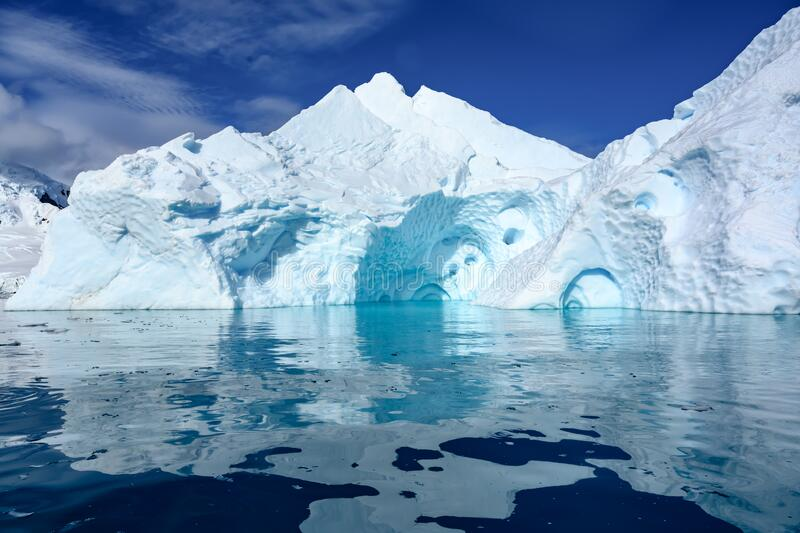Turquoise and white Antarctic iceberg with caves, dark blue sea ice flows and reflections, Paradise Bay, Antarctica royalty free stock photo